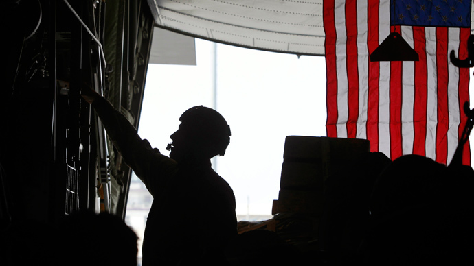A U.S. Air Force C-130 crew member talks on his headset near a U.S. flag as the plane prepares to fly from Bagram Air Base (Reuters / Erik De Castro)