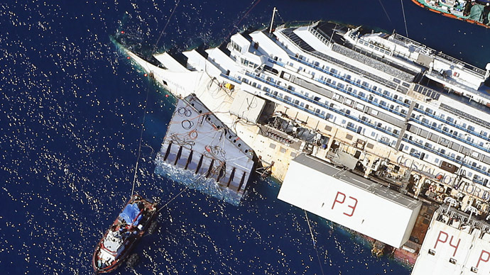 An aerial view shows the Costa Concordia as it lies on its side next to Giglio Island taken from an Italian navy helicopter August 26, 2013. (Reuters/Alessandro Bianchi)