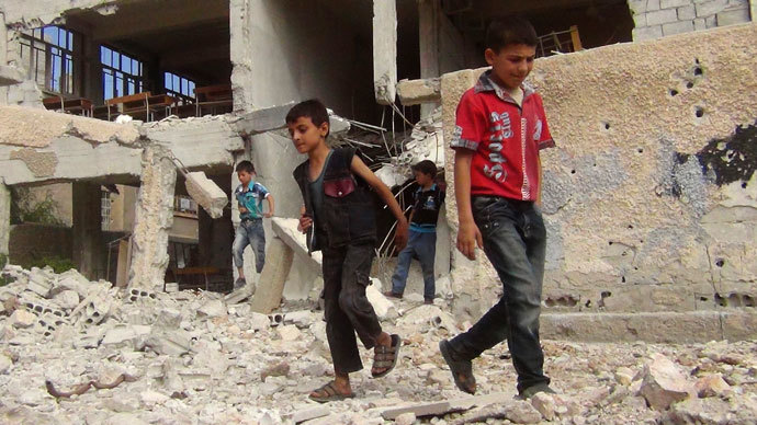 Children walk among debris from a damaged school building in the Damascus suburb of Zamalka.(Reuters / Abou Nidal alshami)