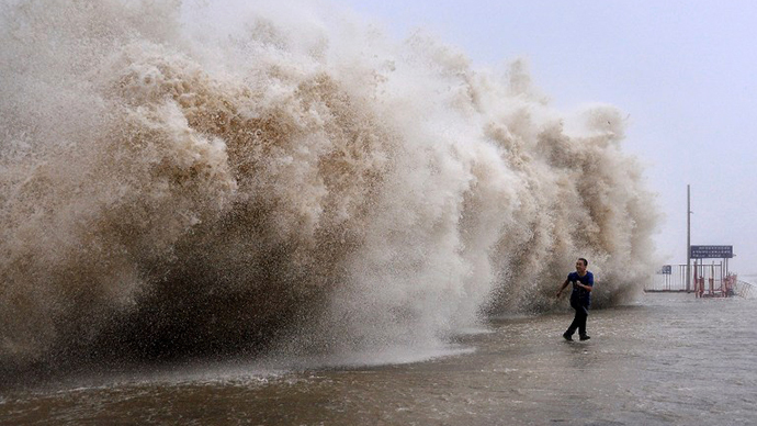 This photo taken on September 22, 2013 shows a man running away from a huge wave pushed up by Typhoon Usagi on a wharf in Shantou, south China's Guangdong province. (AFP Photo)