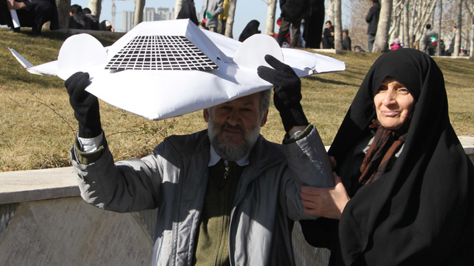 An Iranian couple hold a model of the captured US RQ-170 drone during the 33rd anniversary of the Islamic revolution in Azadi (Freedom) square in Tehran on February 11, 2012. (AFP Photo/Atta Kenare)
