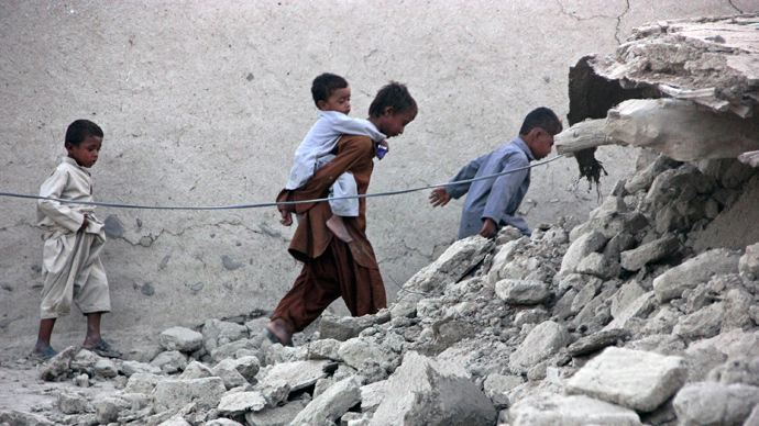 Survivors of an earthquake walk on rubble of a mud house after it collapsed following the quake in the town of Awaran, southwestern Pakistani province of Baluchistan, September 25, 2013 (Reuters / Sallah Jan)