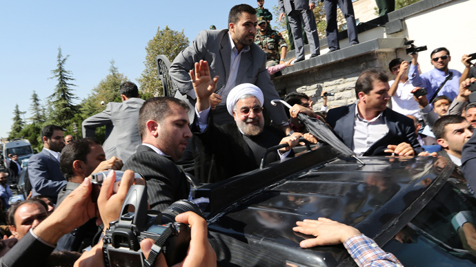 Iranian president Hassan Rouhani waves to supporters as his motorcade leaves Tehran's Mehrabad Airport upon his arrival from New York, on September 28, 2013 (AFP Photo / Atta Kenare)