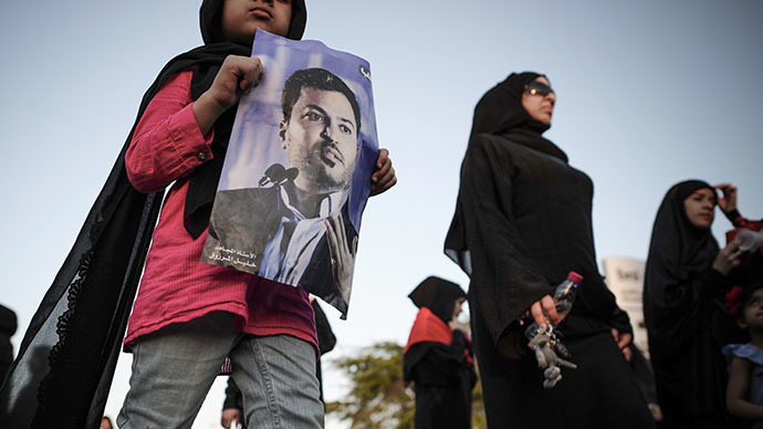 A Bahraini protester holds a portrait of detained former Shiite opposition MP Khalil Marzooq during an anti-government protest in the village of Jannusan, west of the capital Manama, on September 27, 2013. (AFP Photo / Mohammed al-Shaikh)