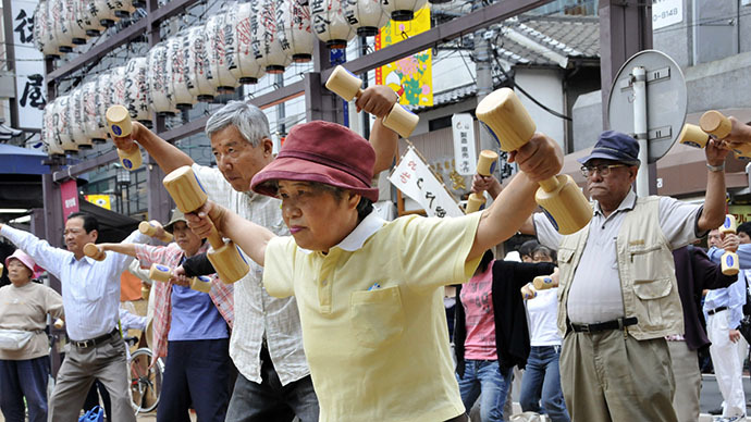 Elderly people work out with wooden dumb-bells in the grounds of a temple in Tokyo (AFP Photo / Yoshikazu Tsuno)