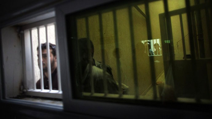Inmates stand near the window of their cell inside the infamous Djeida prison in Tripoli (AFP Photo / Marco Longari)