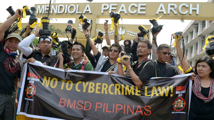 Photographers of different disciplines raise their cameras during a protest near the Presidential Palace to protest the recently-signed Cybercrime Law in Manila on October 13, 2012. (AFP Photo/Jay Directo)