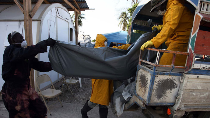 Health workers at a tent city on the outskirts of Haitian capital Port-au-Prince recover the body of cholera victim Ti Rosse Louizi on November 27, 2010. (AFP Photo / Hector Retamal)