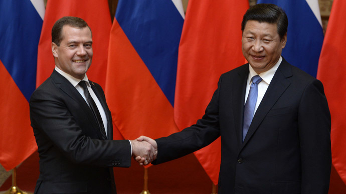 Russian Prime Minister Dmitry Medvedev (L) shakes hands with Chinese President Xi Jinping (R) before a meeting at the Great Hall of the People in Beijing on October 22, 2013. (AFP Phoro/Kota Endo)