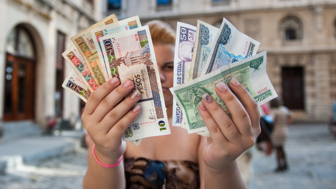 A Cuban shows Cuban Pesos CUP (Left hand) and Convertible Pesos CUC (AFP Photo / Yamil Lage)