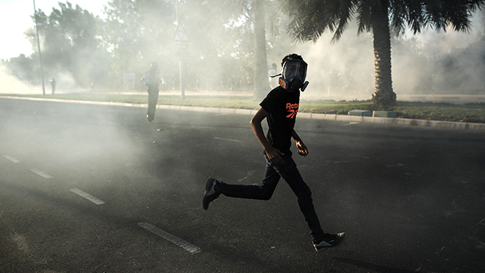 A Bahraini protester, wearing a mask, runs away from tear gas and bird shot fired by riot police during clashes following the funeral of Ali Khalil Sabbagh in the village of Bani Jamrah, west of Manama, on October 23, 2013. (AFP Photo / Mohammed al-Shaikh)