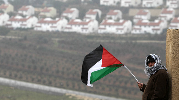 A Palestinian man waves his national flag on the sidelines of a march organized by inhabitants of the West Bank village Nabi Saleh to protest against the expansion of Jewish settlements on Palestinian land. (AFP Photo/Abbas Momani)