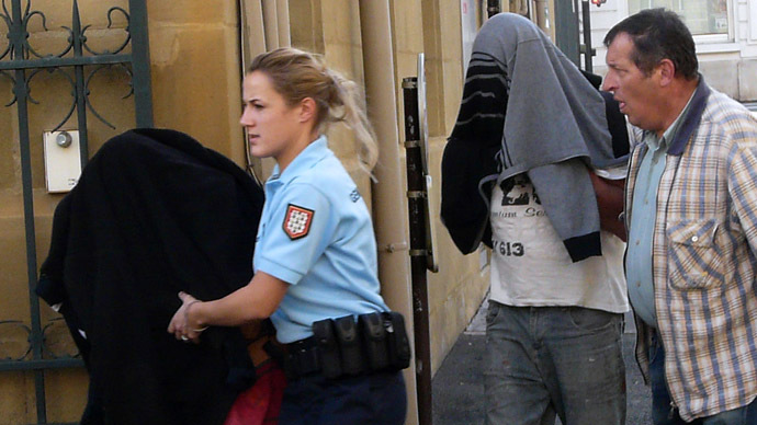 A couple who kept their newborn child locked in the trunk of a car for presumably over a year are escorted by police into a court in Brive-la-Gaillarde, on October 28, 2013. (AFP Photo/Eric Porte)