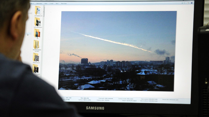 A man in Moscow looks at a computer screen displaying a picture reportedly taken in the Urals city of Chelyabinsk on February 15, 2013, showing the trail of a meteorite above a residential area of the city. (AFP Photo)