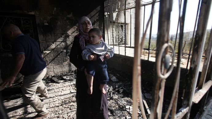 Palestinians look at damages inside a house that was fired overnight by suspected Jewish extremists in an apparent revenge attack on November 14, 2013 in Sinjil, a village in the West Bank, northeast of Ramallah (AFP Photo / Abbas Momani)