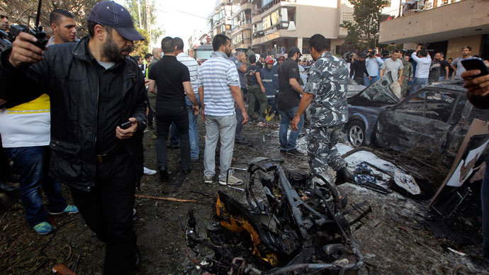 A security personnel officer looks back as he walks past a burnt motorcycle at the site of explosions near the Iranian embassy in Beirut November 19, 2013.(Reuters / Mahmoud Kheir)