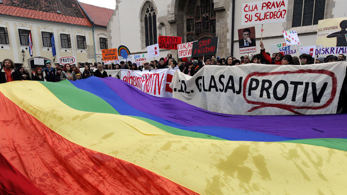 Croatian gay rights supporters hold a giant rainbow flag outside the parliament building in Saint Marko Square in Zagreb during a protest on November 30, 2013.(AFP Photo / STR)
