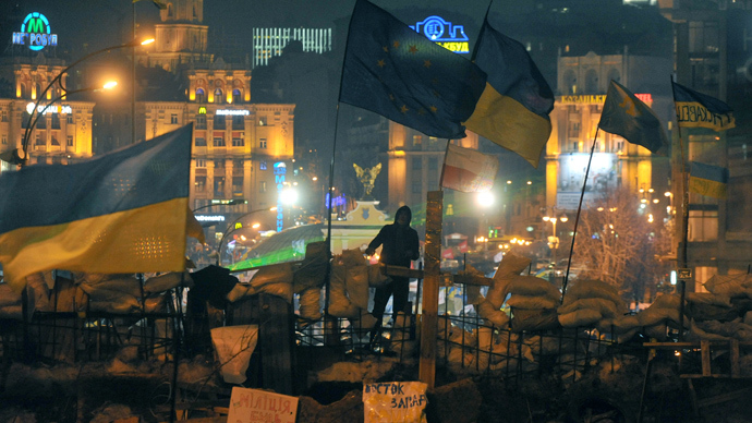 An activist stands atop a barricade flanked by the European Union and Ukrainian flags during an opposition rally on Independence Square in central Kiev on December 17, 2013 (AFP Photo / Genia Savilov)