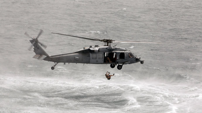 A U.S. Navy diver cuts himself free after getting entangled with his safety device as he jumps from a USS Navy helicopter to perform a mine-sweeping exercise during the International Mine Countermeasures Exercise (IMCMEX) in the Middle East Gulf May 14, 2013.(Reuters / Hamad I Mohammed)
