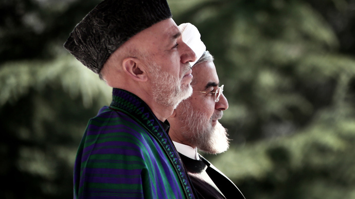 Iranian President Hassan Rouhani (R) and his Afghan counterpart Hamid Karzai (L) listen to their national anthems during a welcoming ceremony at Tehran's Saadabad Palace on December 8, 2013. (AFP Photo / Behrouz Mehri)