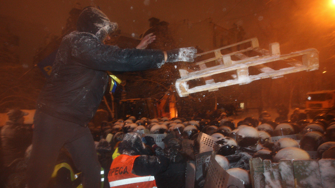 A man throws a wooden tray as riot police gather near a barricade set up by supporters of EU integration in Kiev, December 9, 2013 (Reuters / Valentyn Ogirenko)