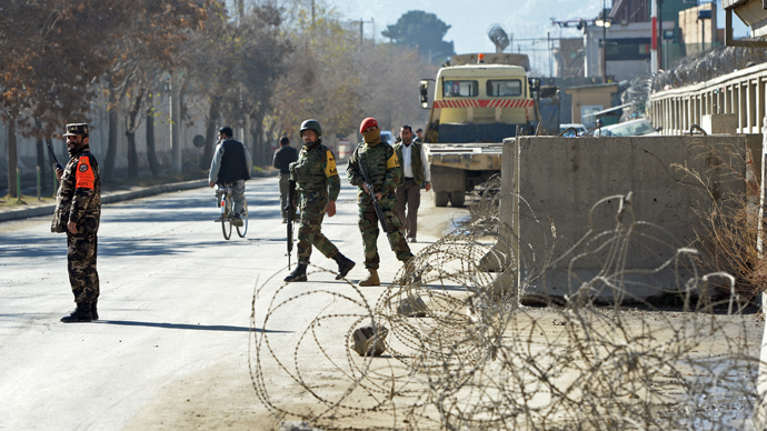 Afghanistan security forces keep watch at the main gate of the National Directorate of Security (NDS), where an accidental explosion in an arms depot shook central Kabul, on December 12, 2013. (AFP Photo / Massoud Hosaini)