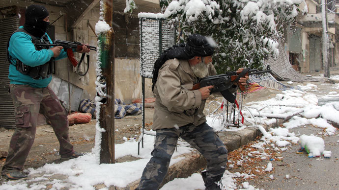 Rebel fighters hold their weapons as they stand amidst snow during clashes with Syrian pro-government forces in the Salaheddin neighbourhood of Syria's northern city of Aleppo on December 11, 2013.(AFP Photo / Medo Halab)