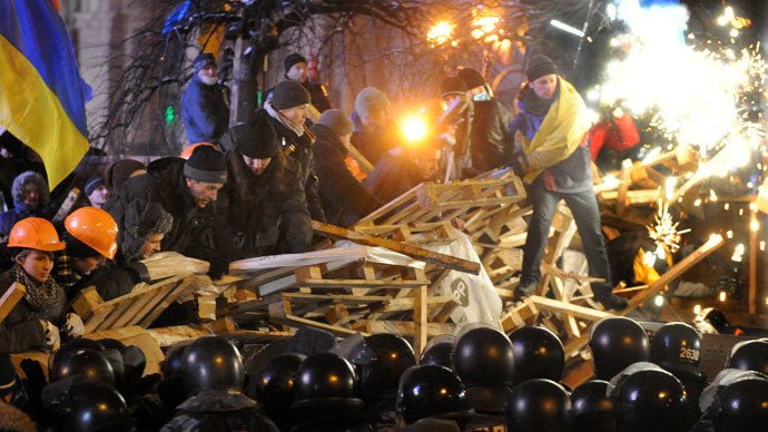 Anti-Yanukovych protesters defend their barricades in front of anti-riot police on Independence Square in Kiev, early on December .(AFP Photo / Viktor Drachev)