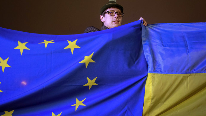 A protester holds Ukrainian and European Union flags during a rally to support euro integration in central Kiev  (Reuters/Gleb Garanich)