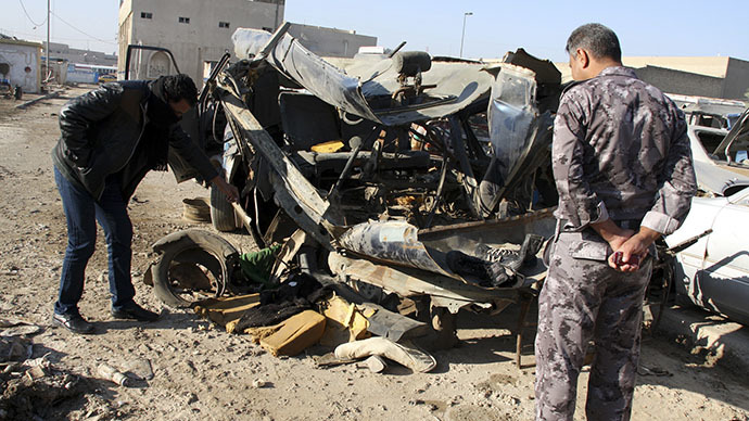 An Iraqi policeman  looks at a damaged vehicle after a car bomb attack in Baghdad 16, 2013 (Reuters / Wissm al-Okili)
