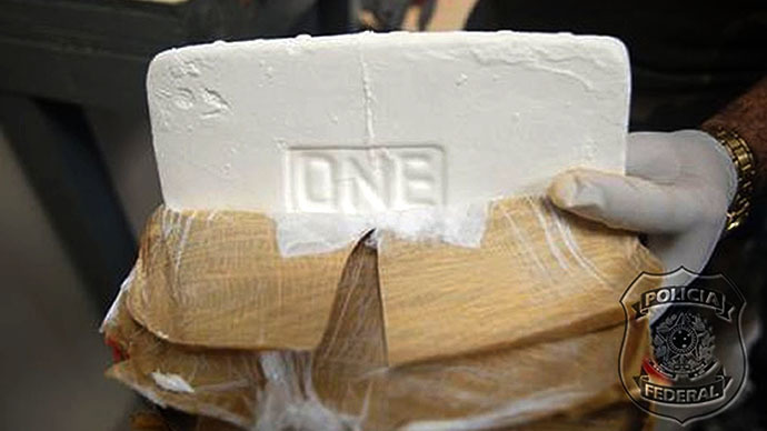 A policeman holding a cocaine brick (AFP Photo / Policia Federal)