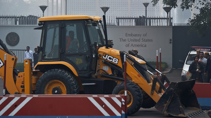 Indian policemen watch as a bulldozer removes a barricade in front of the US Embassy in New Delhi on December 17, 2013 (AFP Photo)