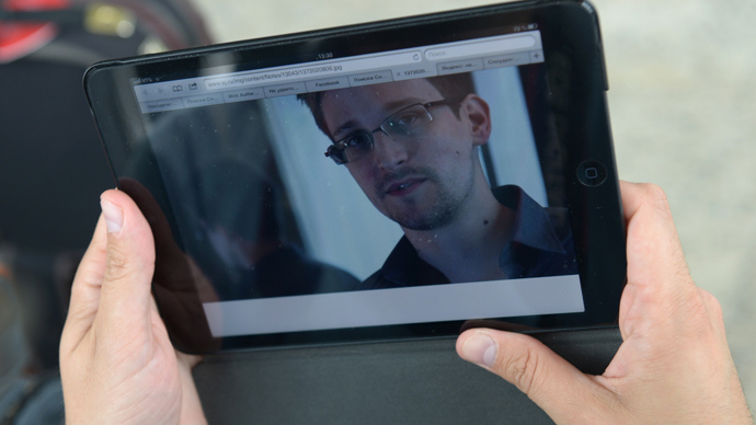 A journalist studies a photo of former CIA employee Edward Snowden, (RIA Novosti / Valeriy Melnikov)