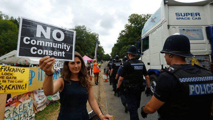 Local resident Kate Room demonstrates as police escort a lorry to the entrance of a drill site run by Cuadrilla Resources, in the village of Balcombe in southern England September 3, 2013.(Reuters / Luke MacGregor)