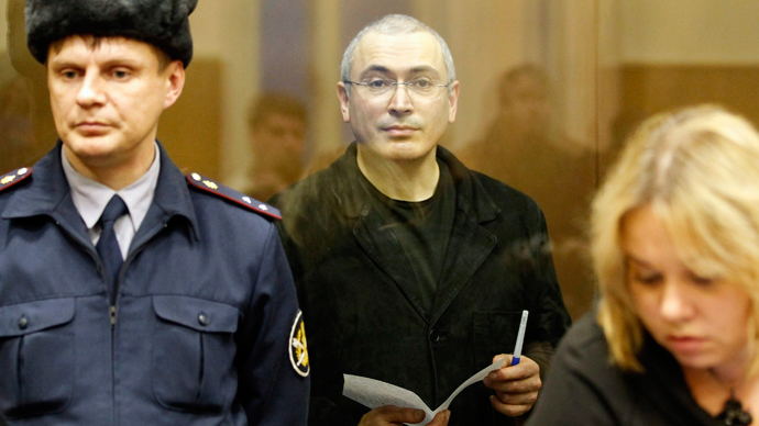 Jailed Russian former oil tycoon Mikhail Khodorkovsky (C) holds a paper as he stands in the defendants' cage during a court session in Moscow December 30, 2010. (Reuters / Tatyana Makeyeva)