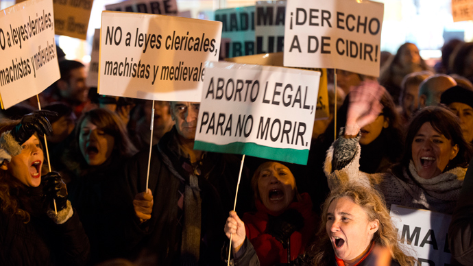 """People hold placards reading """"No to clerical, macho and medieval laws"""" (L), """"Legal abortion, to don't die"""" and """"The right to decide"""" during a pro-choice demonstration in Madrid against the government's plan to tighten abortion laws on December 20, 2013 (AFP Photo)"""