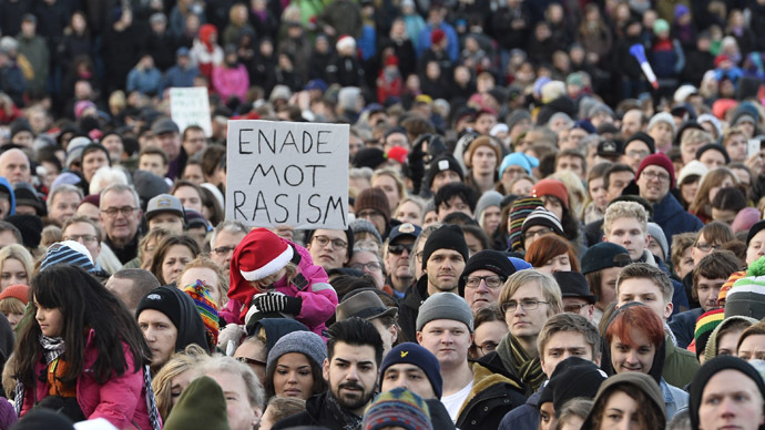 "People demonstrating against nazism and racism hold a placard reading ""united against racism"" in the Stockholm suburb Karrtorp, Sweden on December 22, 2013. (AFP/TT News Agency)"