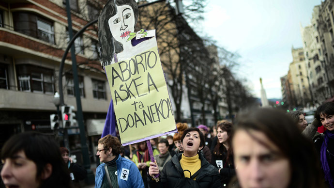 "A demonstrator carries a sign reading ""Costless And Free Abortion"" during a pro-choice protest against the government's proposed new abortion law in Bilbao, December 21, 2013. (Reuters/Vincent West)"
