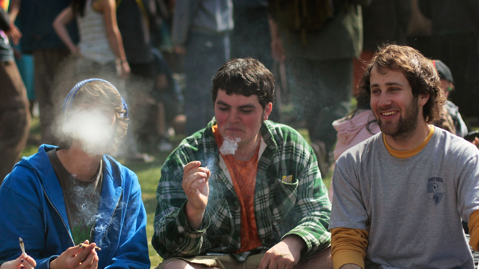 "(FILES) Young men smoke a marijuana cigarette during a ""smoke out"" with thousands of others at the University of Colorado in Boulder, Colorado. (AFP Photo / Chris Hondros)"