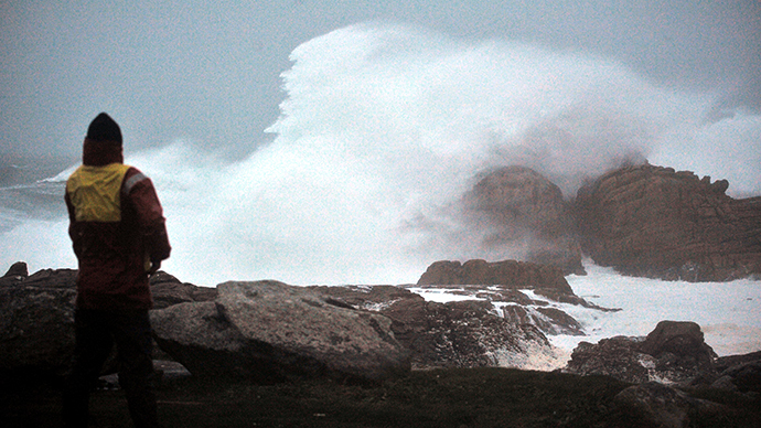 A man looks at waves crashing onto rocks as a storm brings heavy winds to Saint-Guenole, western France, on December 23, 2013. (AFP Photo / Frank Perry)