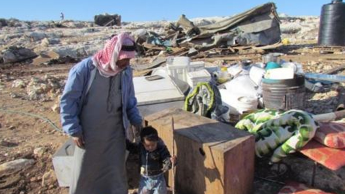 Father and child amongst their belongings following the demolition. Image from UNRWA