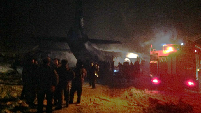 Firemen working next to the tail portion of the crashed An-12 cargo plane near the Siberian city of Irkutsk on December 26, 2013. (Photo: 38.mchs.gov.ru)