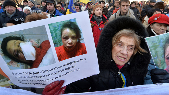 A Protester holds photos of Tetyana Chornovol, popular Ukrainian journalist and opposition activist, during the rally at the Internal Affairs Ministry in Kiev on December 26, 2013. (AFP Photo / Sergei Supinsky)