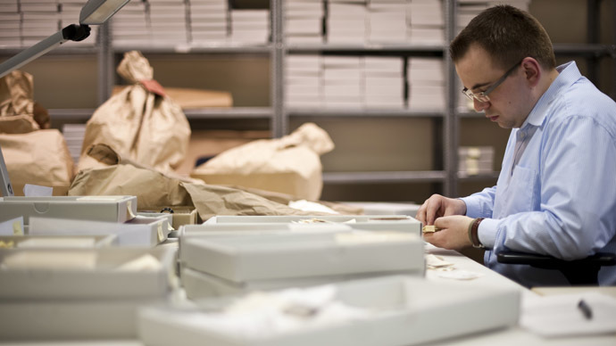 A worker in the former headquarters of the Stasi (East German communist secret police) sorts through hundreds of thousands of torn or shredded Stasi documents earmarked for destruction after the fall of the Berlin wall in 1989 (AFP Photo/John Macdougall)