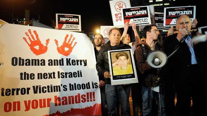"Israeli protesters hold placards, one of them reading ""Obama and Kerry the next Israeli terror Victim's blood is on your hands"", as they demonstrate in the city of Tel Aviv on December 26, 2013 against the release of Palestinian prisoners. (AFP Photo / David Buimovitch)"