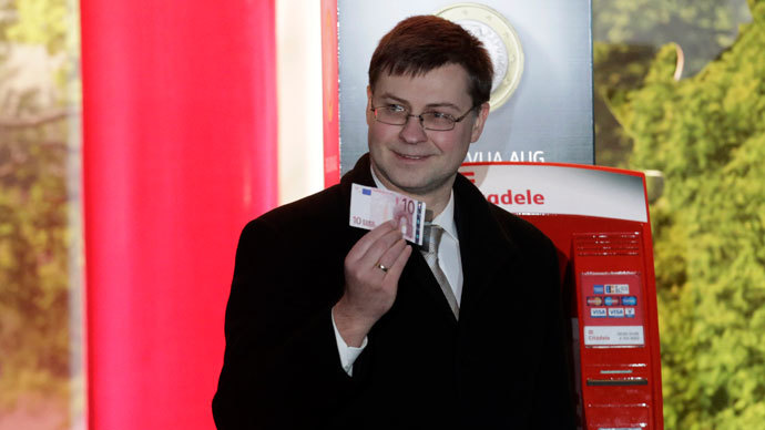 Latvia's Prime Minister Valdis Dombrovskis poses for the media with the euro banknote during an official event in Riga January 1, 2014.(Reuters / Ints Kalnins)