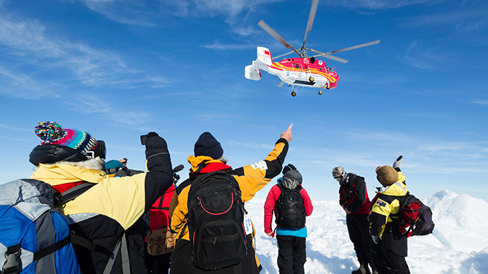 This image taken by expedition doctor Andrew Peacock of www.footloosefotography.com on January 2, 2014 shows a helicopter from the nearby Chinese icebreaker Xue Long above passengers from the stranded Russian ship MV Akademik Shokalskiy as the first helicopter rescue takes place after over a week of being trapped in the ice off Antarctica. (AFP Photo)