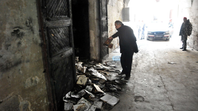 "A man inspects burnt books on January 4, 2014 in north Lebanon's majority Sunni city of Tripoli a day after a decades-old library owned by a Greek Orthodox priest was torched after ""a pamphlet was discovered inside one of the books that was insulting to Islam and the prophet Mohammad"" said a source, who spoke to AFP on condition of anonymity. (AFP Photo)"