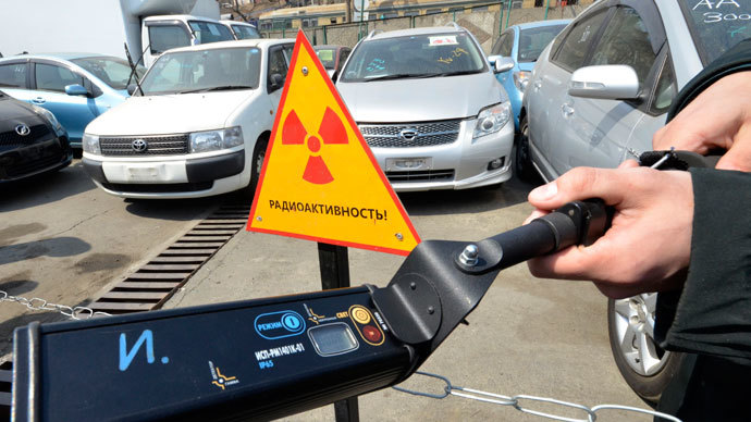 A customs officer holds up a device used for measuring radiation levels, while standing in front of vehicles delivered from Japan, in Russia's far eastern city of Vladivostok.(Reuters / Yuri Maltsev)