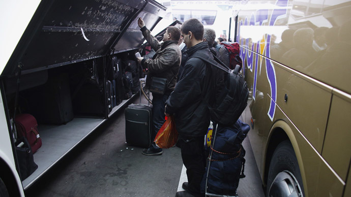 People put their luggage in a bus departing from Sofia's central bus station to London via Austria, Germany and France January 2, 2014. (Reuters/Stoyan Nenov)
